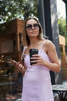 Asiatische frau im rosa kleid, die draußen steht und smartphone und tasse kaffee hält