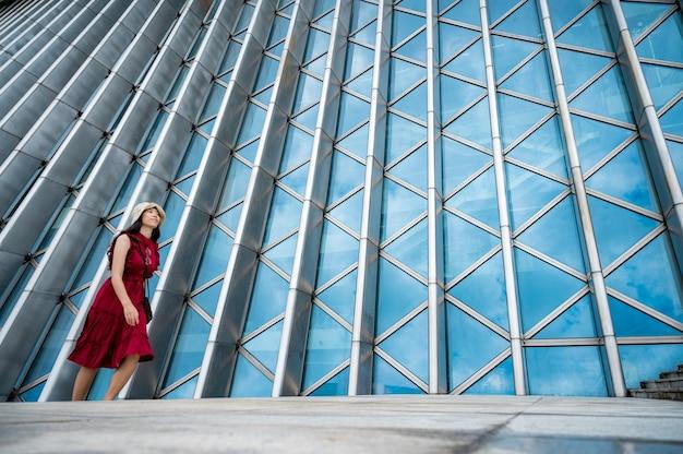 Asiatische frau im roten kleid am modernen gebäude, weibliches mädchen mit städtischem stadtlebensstil