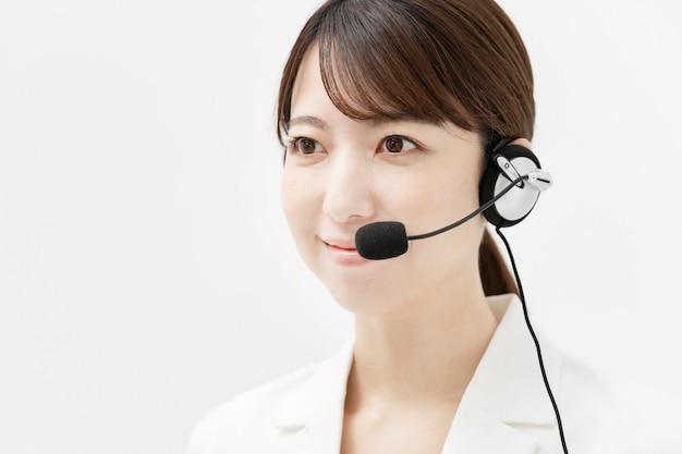 Asiatische frau im weißen anzug, der ein headset mit einem lächeln trägt