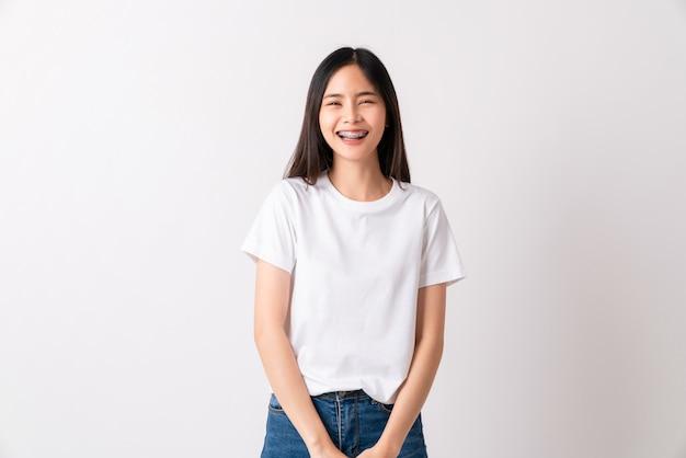 Asiatische frau im weißen t-shirt und stehen lächelnd mit klammern auf weißem hintergrund.