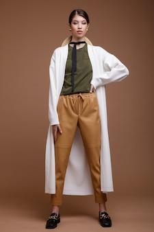 Asiatische frau in beige lederhose weiße lange strickjacke grüner t-shirt gürtel auf braunem hintergrund