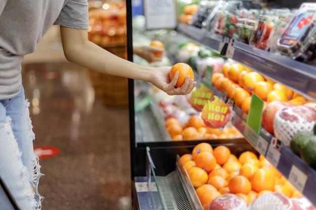 Asiatische frau in der freizeitkleidung, die im supermarkt einkauft