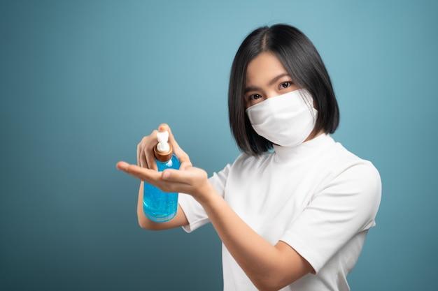 Asiatische frau in der gesichtsmaske, die hände unter verwendung des händedesinfektionsgels wäscht, um viren zu vermeiden