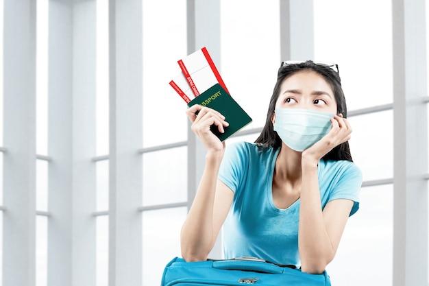 Asiatische frau in der gesichtsmaske mit einem koffer, der ticket und pass auf dem krankenhaus hält. ärztliche untersuchung vor reiseantritt