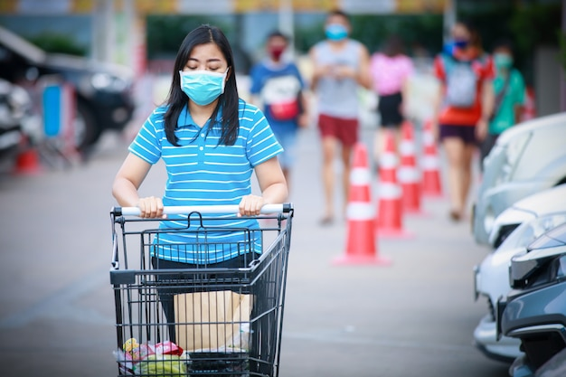 Asiatische frau in der medizinischen gesichtsmaske, die wagen zum auto nach dem einkaufen im supermarkt schiebt
