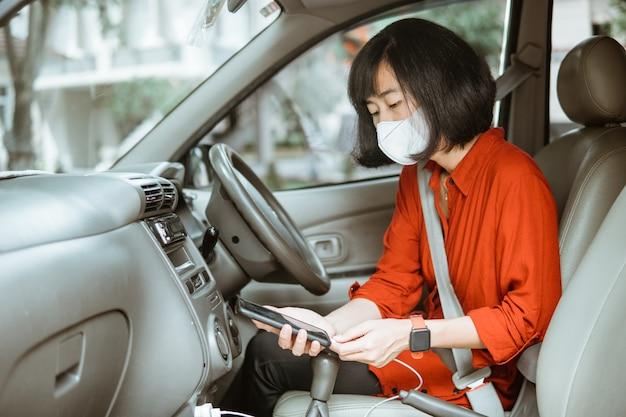 Asiatische frau in der schutzmaske, die ein auto auf straße fährt. laden sie ihr telefon auf