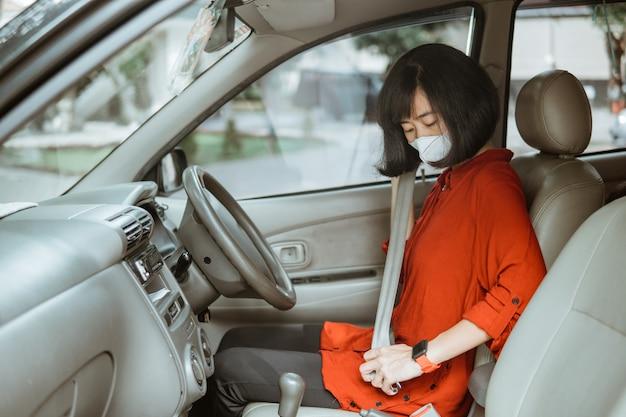 Asiatische frau in der schutzmaske, die ein auto auf straße fährt. sicheres reisen und sicherheitsgurt anlegen