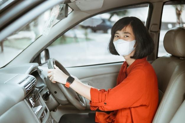 Asiatische frau in der schutzmaske, die ein auto auf straße fährt. sicheres reisen.
