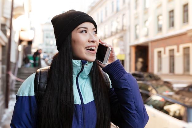 Asiatische frau in der warmen kleidung, die am telefon spricht