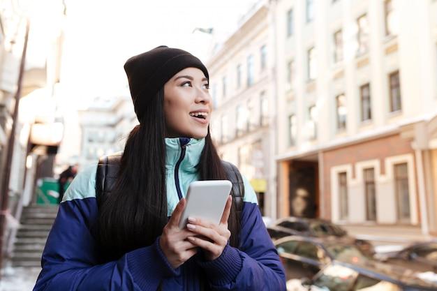 Asiatische frau in der warmen kleidung, die telefon hält