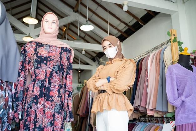 Asiatische frau in einem hijab, die eine maske trägt und die hände kreuzt