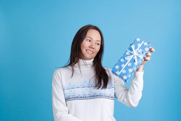 Asiatische frau in einem pullover, der ein blaues geschenk betrachtet