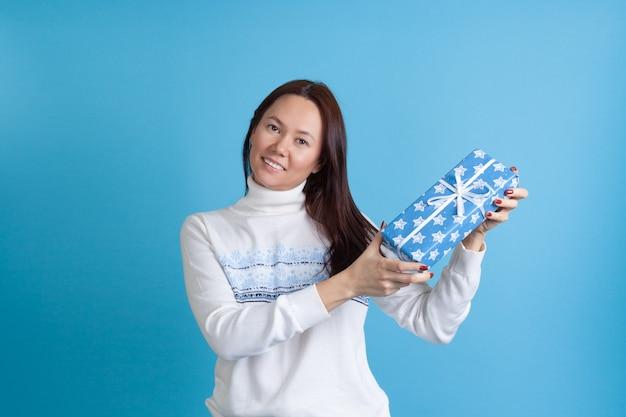 Asiatische frau in einem pullover, der schön eine geschenkbox zeigt