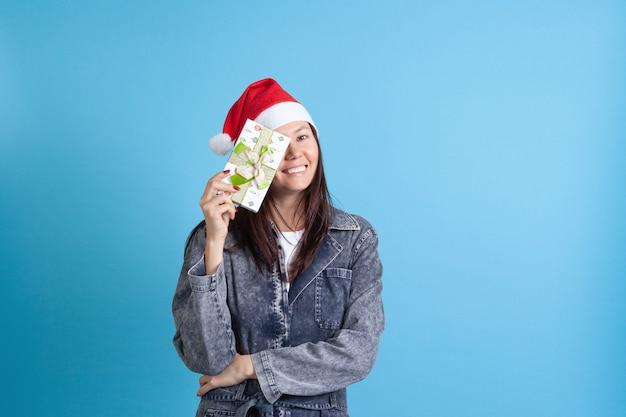 Asiatische frau in einem weihnachtskranz, der ein auge hinter kasten versteckt