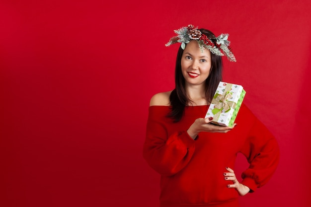 Asiatische frau in einem weihnachtskranz, der eine grüne geschenkbox hält