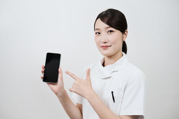Asiatische frau in einem weißen kittel, die ein smartphone bedient