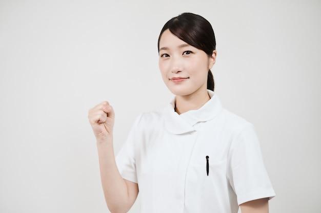 Asiatische frau in einem weißen kittel macht eine mutpose