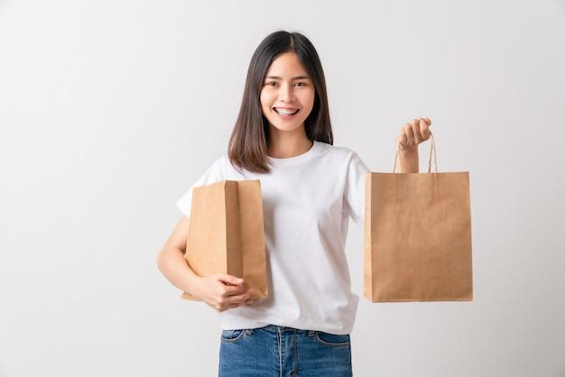 Asiatische frau in einem weißen t-shirt und halten braune leere bastelpapiertüte auf weißem hintergrund.