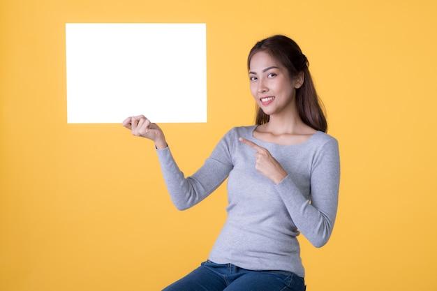 Asiatische frau in freizeitkleidung, die leeres leeres brett hält und mit dem finger auf gelbem hintergrund zeigt