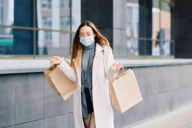 Asiatische frau in mantel, brille und medizinischer maske steht auf der straße