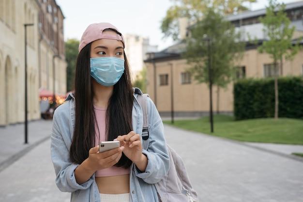 Asiatische frau in medizinischer maske, die handy hält und im freien wegschaut