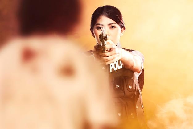 Asiatische frau in polizeiweste mit einer waffe in der hand, die bereit ist, zombies mit dramatischem hintergrund anzugreifen