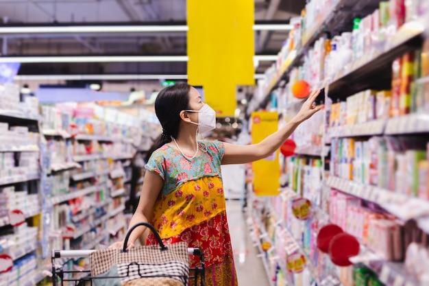 Asiatische frau in schutzmaske beim einkaufen im supermarkt während der covid19-pandemie