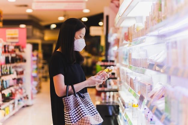 Asiatische frau in schutzmaske, die eine flasche shampoo im supermarkt hält