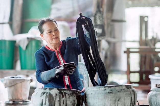 Asiatische frau in traditioneller kleidung indigofärben bevor sie zu stoff gewebt wird, der ein produkt ist, das einen guten ruf für die provinz sakon nakhon in thailand hat.