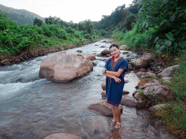 Asiatische frau in traditioneller, legerer kleidung aus nordthailand, die im fließenden fluss mit großen felsen im frischen grünen wald steht, reiseziel im dorf sapan, nan, thailand?