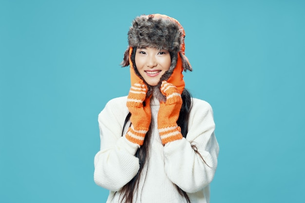Asiatische frau in warmem hut und handschuhen auf blauem hintergrund lächeln wintermodell