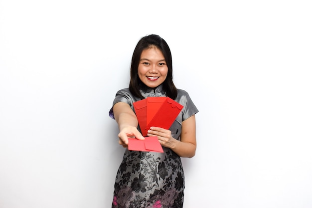 Asiatische frau kleid traditionelle cheongsam tun einige pose und halten roten umschlag angpau