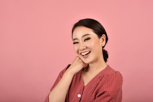 Asiatische frau lacht und genießt auf rosa hintergrund