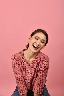 Asiatische frau lacht und genießt auf rosa wand, porträt der glücklich lächelnden frau mittleren alters in der freizeitkleidung