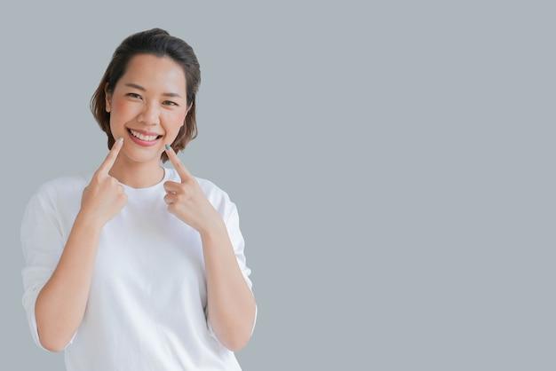 Asiatische frau lächelnd mit zahnschienenhalter unsichtbar auf grauem hintergrund isoliert