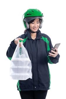 Asiatische frau lieferung essen. kurierin mit lebensmitteln auf einer plastiktüte, die lebensmittel liefert