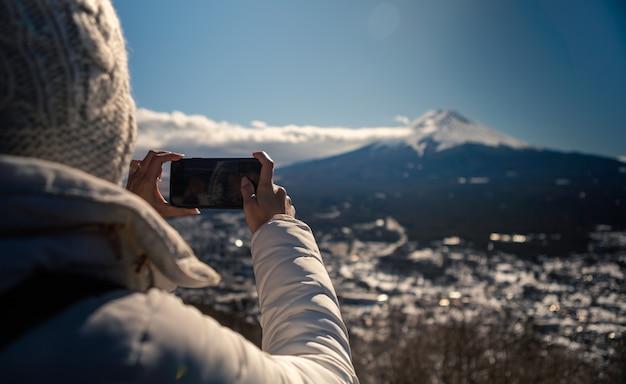 Asiatische frau macht foto mit smartphone zum schönen fuji-berg mit schneedecke auf der spitze in japan. tourist, der mit dem telefon eine japanische schönheitslandschaft im winter fotografiert
