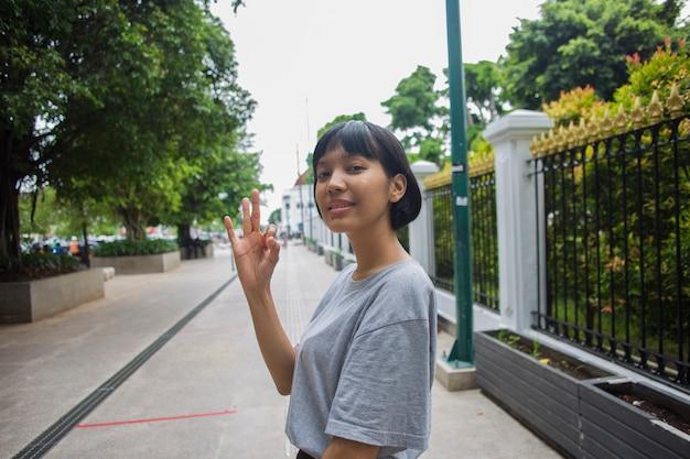 Asiatische frau macht im öffentlichen raum eine geste mit dem daumen nach oben
