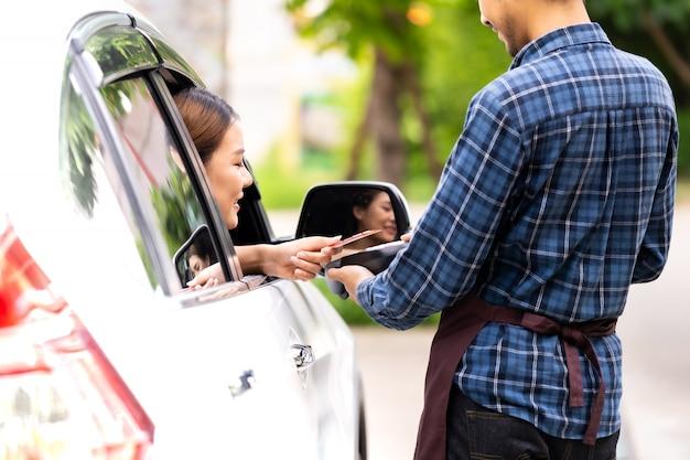 Asiatische frau macht kontaktlose zahlung mit kreditkarte für drive-through-service