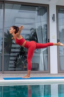 Asiatische frau macht yoga außerhalb der villa am schwimmbad frau in roter sportkleidung macht yoga-posen auf der matte
