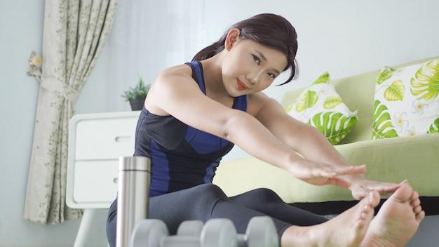 Asiatische frau macht yoga zu hause und wärmt sich auf, um sich zu beugen
