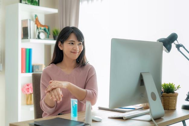 Asiatische frau mit alkohol antiseptischen gel reinigung hände häufig, verhindern sie eine infektion