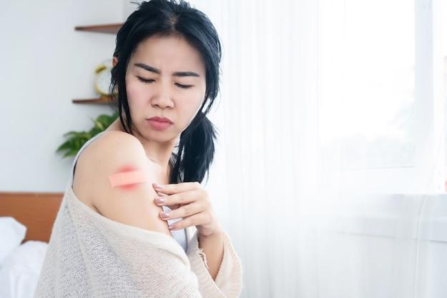 Asiatische frau mit allergieausschlag an der schulter nach der impfung gegen covid19