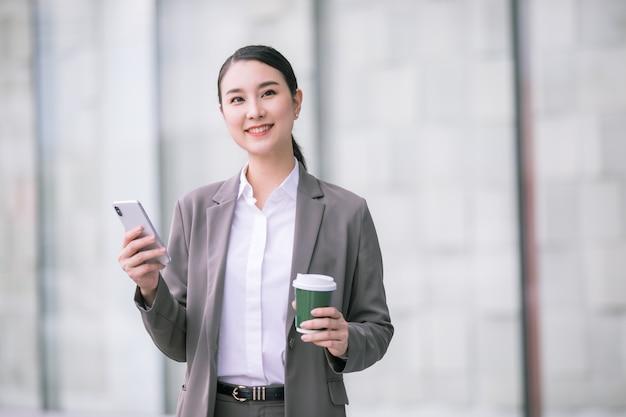Asiatische frau mit dem smartphone, das gegen straßen verschwommenes gebäude steht. modegeschäftsfoto des schönen mädchens in der lässigen suite mit telefon und tasse kaffee.