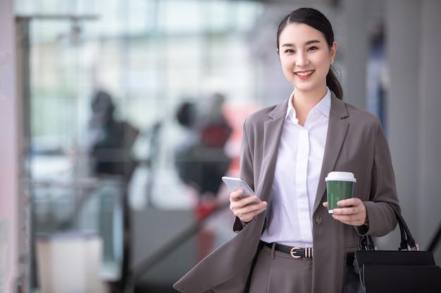 Asiatische frau mit dem smartphone, das gegen straßen verschwommenes gebäude steht. modegeschäftsfoto des schönen mädchens in der lässigen suite mit telefon und tasse kaffee