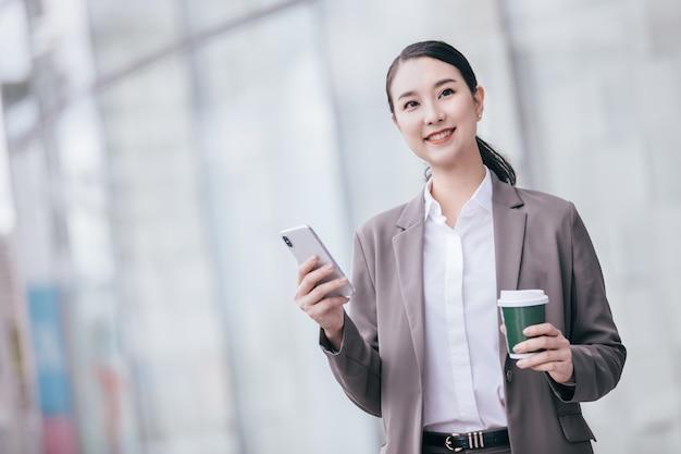 Asiatische frau mit dem smartphone, das gegen straßen verwischte gebäudehintergrund steht.