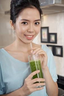 Asiatische frau mit einem glas smoothie