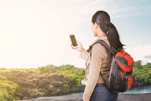 Asiatische frau mit einem rucksack, der smartphone mit einem seeblick und blauem himmel hält. welttourismustag