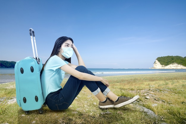 Asiatische frau mit einer gesichtsmaske, die mit einem koffer am strand sitzt. reisen in der neuen normalität