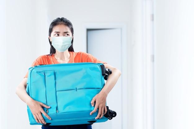 Asiatische frau mit einer gesichtsmaske, die mit einem koffer auf dem krankenhaus trägt. ärztliche untersuchung vor reiseantritt